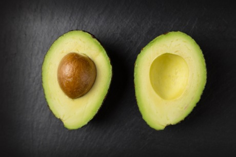 Avacado halves on dark background